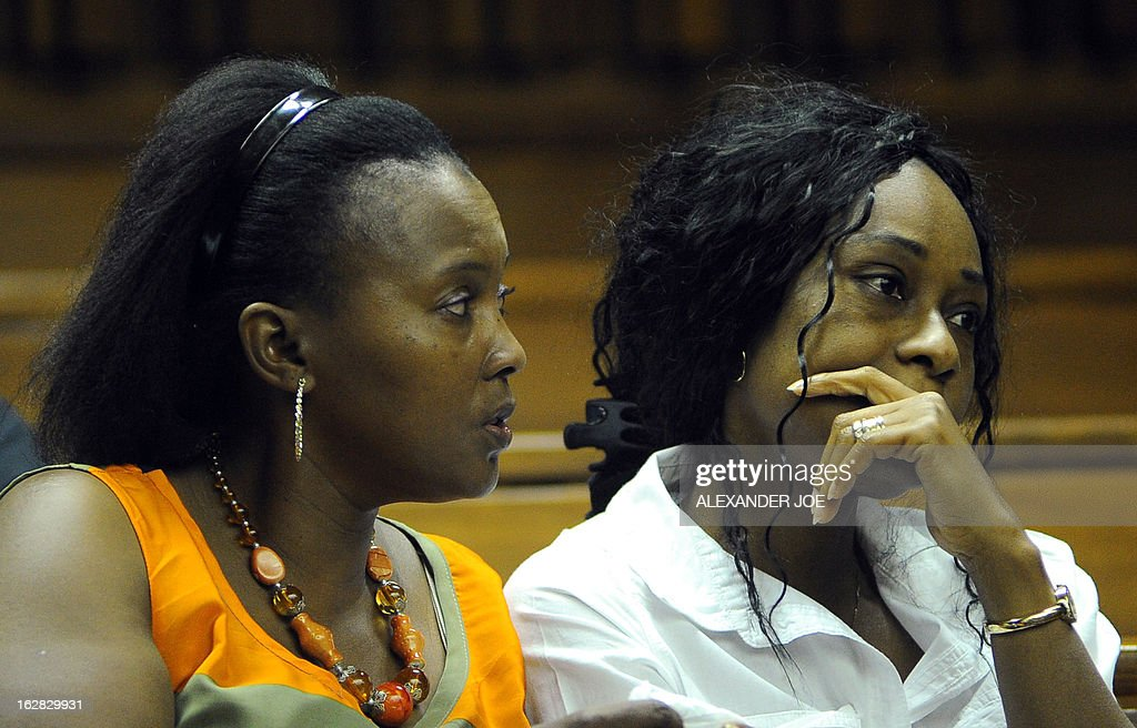 Azuka Okah (R), wife of Nigerian militant leader Henry Okah, reacts in court after her husband's case was posted because he changed his legal team at Johannesburg High Court on February 28, 2013. Okah is convicted of 13 terrorism charges, including the 2010 independence day bombings in Abuja. Okah was found guilty of masterminding attacks including twin car bombings in Abuja on October 1, 2010, and two explosions in March 2010 in the southern Nigerian city of Warri, a major hub of the oil-rich Delta region. He faces a minimum term of life in prison.
