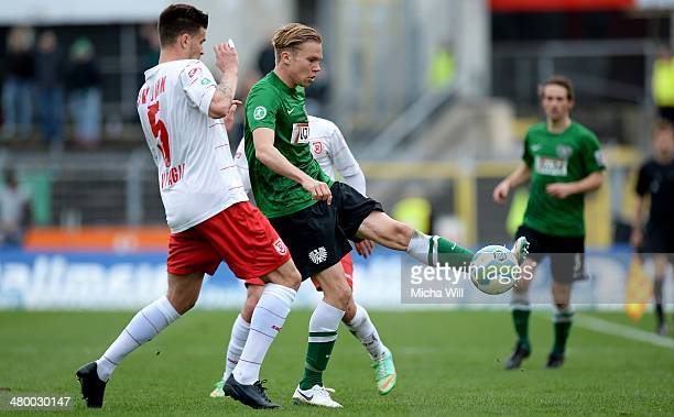 Azur Velagic and Aias Aosman of Regensburg challenge Dennis Grote of Muenster during the Third League match between Jahn Regensburg and Preussen...