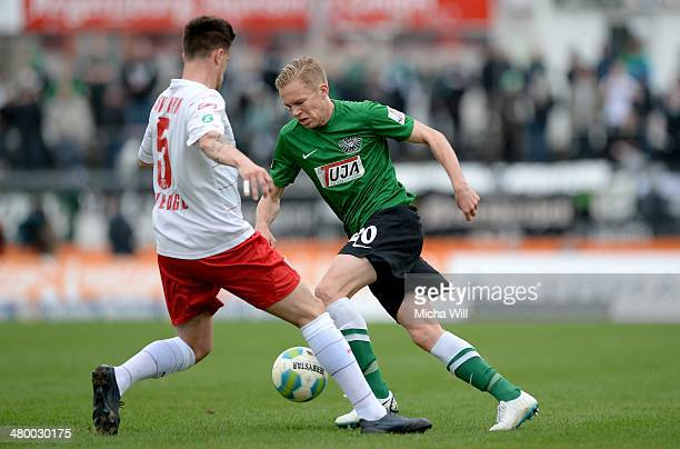 Azur Velagic of Regensburg challenges Dennis Grote of Muenster during the Third League match between Jahn Regensburg and Preussen Muenster at...