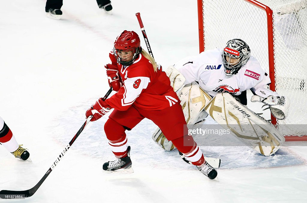 Azusa Nakaoku (R) of Japan fights for puck with Line Ernst (L) of Denmark during the Women's ice hockey Olympic qualification group C match Denmark vs Japan in Poprad on February 10, 2013.