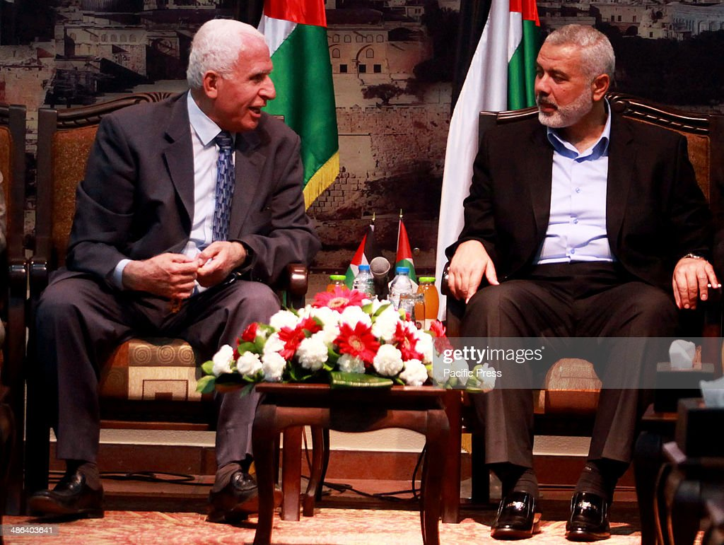 Azzam AlAhmed a senior Fatah official and head of the Hamas government Ismail Haniyeh attend a meeting in Gaza City on April 22 2014 The Palestine...