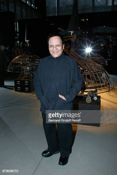 Azzedine Alaia poses in front the works of JeanPaul Goude during the 'Societe des Amis du Musee d'Art Moderne du Centre Pompidou' Dinner Party Held...