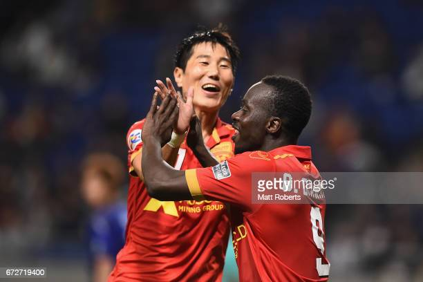 Baba Diawara of Adelaide United celebrates scoring a goal with Jaesung Kim during the AFC Champions League Group H match between Gamba Osaka v...