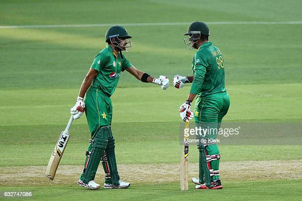Babar Azam of Pakistan congratulates teammate Sharjeel Khan after Khan reached 50 runs during game five of the One Day International series between...