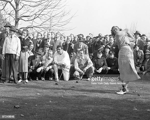 Babe Didrikson Zaharias tees off at second hole at Fresh Meadow Club in Flushing Long Island Holding their clubs as they watch are Sylva Annenberg...