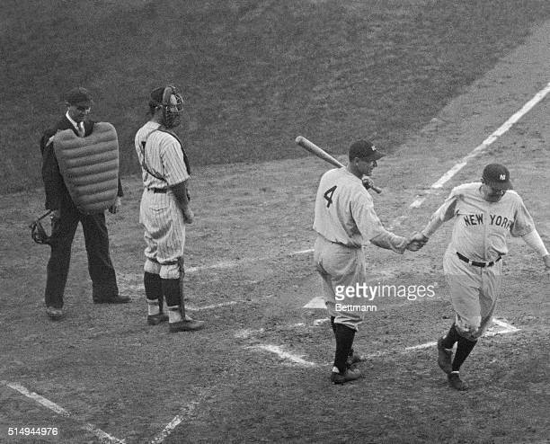 Babe Ruth is greeted at the plate by Lou Gehrig after hitting a homer in the 3rd game of the the World Series This is the home run that was...