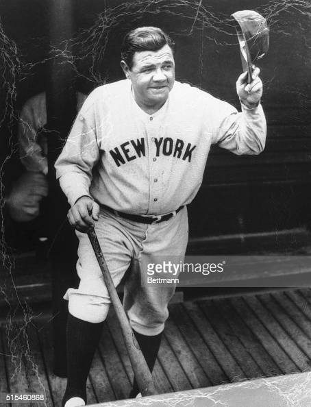 Babe Ruth is shown in this closeup standing in the dugout holding his bat and waving his hat