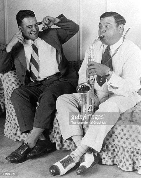 Babe Ruth New York Yankees outfielder blowing into a saxophone on the right deafens teammate and first baseman Lou Gehrig in a photo opportunity...