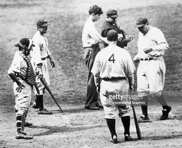 Babe Ruth New York Yankees outfielder is greeted at home plate by Lou Gehrig number 4 and Yankee batboy second from left while Washington Senators...