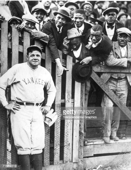 Babe Ruth New York Yankees outfielder poses with African American fans somewhere in the southeast during the trip north from spring training before...