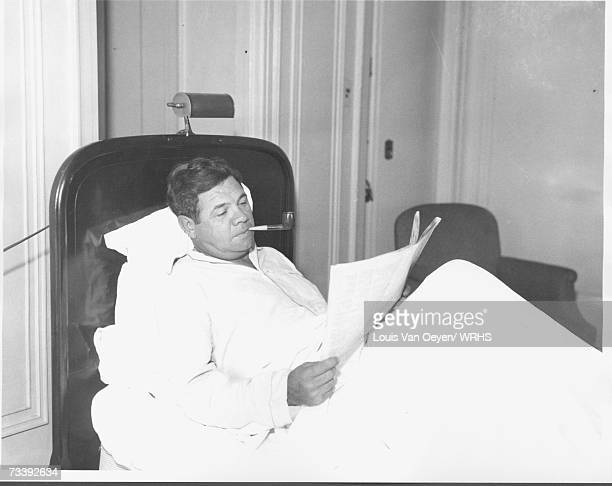 Babe Ruth reading newspaper in bed at the Hotel Cleveland Ruth was confined to bed after being struck in the right ankle by a line drive during the...