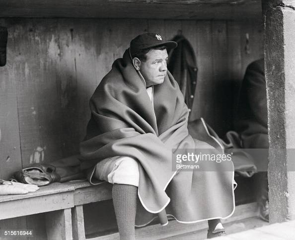 Babe Ruth sits wrapped in a blanket in the dugout at Ebbets Field prior to an exhibition game with the Brooklyn Dodgers