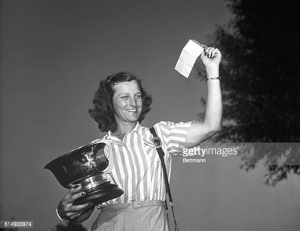 Babe Zaharias holding Women's National Open Golf Tourney trophy and waving check representing first prize of $120000