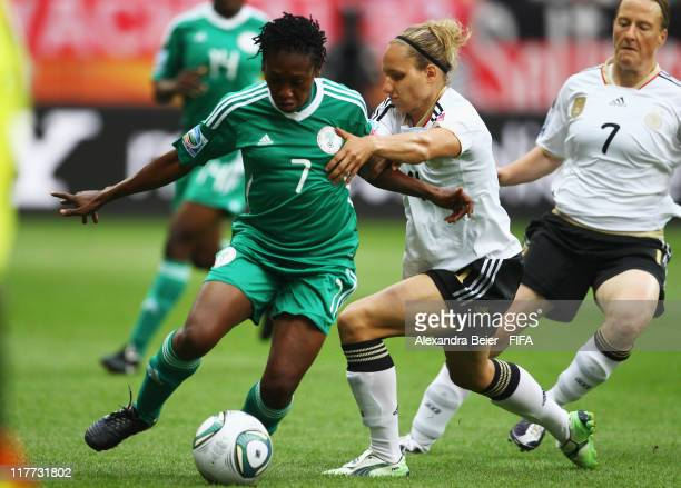 Babett Peter of Germany fights for the ball with Stella Mbachu of Nigeria during the FIFA Women's World Cup 2011 Group A match between Germany and...