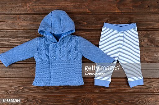 Babies blue knitted cardigan and striped pants on wooden backgro : Stock Photo