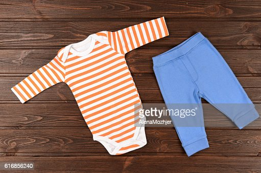 Babies bodysuits and pants on wooden background. Baby clothes : Stock Photo