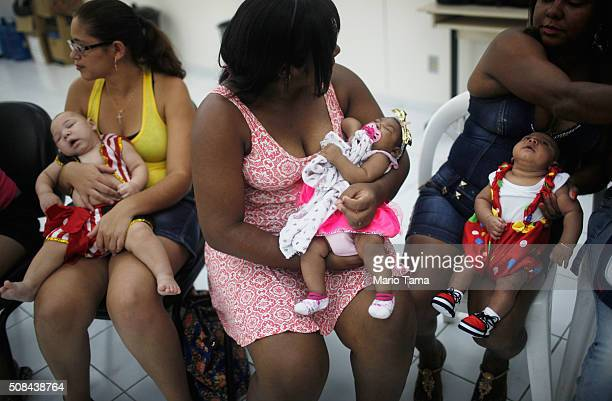 Babies dressed in Carnival outfits born with microcephaly are held by their mothers at a Carnival party held for babies with the condition in a...