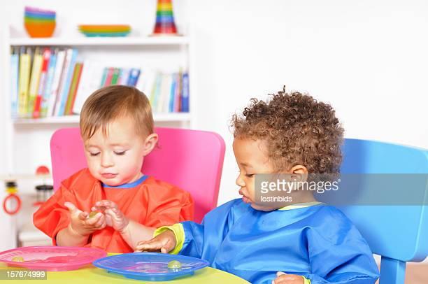 Babies Enjoying Fruit During Mealtime In A Nursery Setting