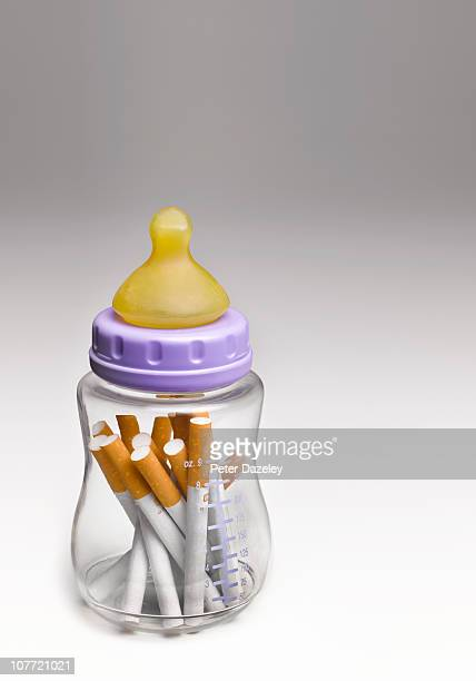 Babies feeding bottle with cigarettes