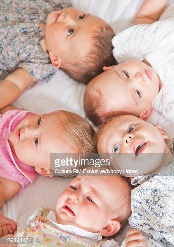 Babies laying on bed together : Bildbanksbilder