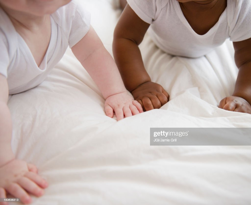 Babies laying on floor together : Stock Photo