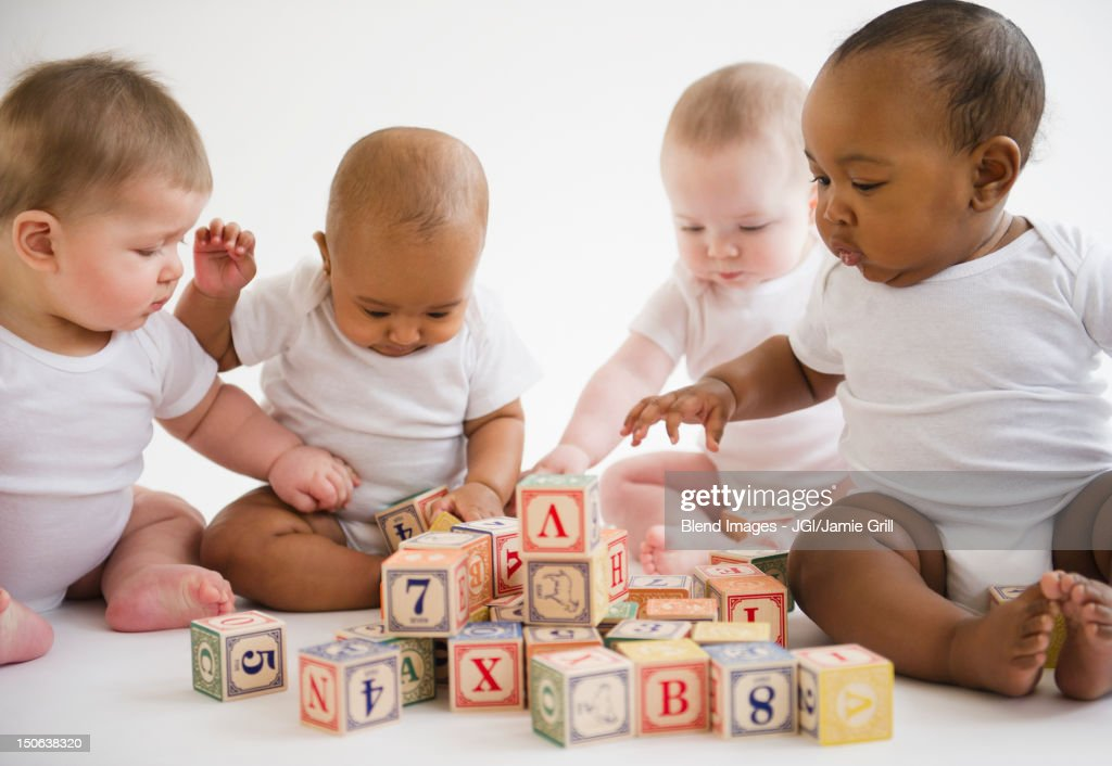 Babies sitting on floor playing with blocks : Stock Photo