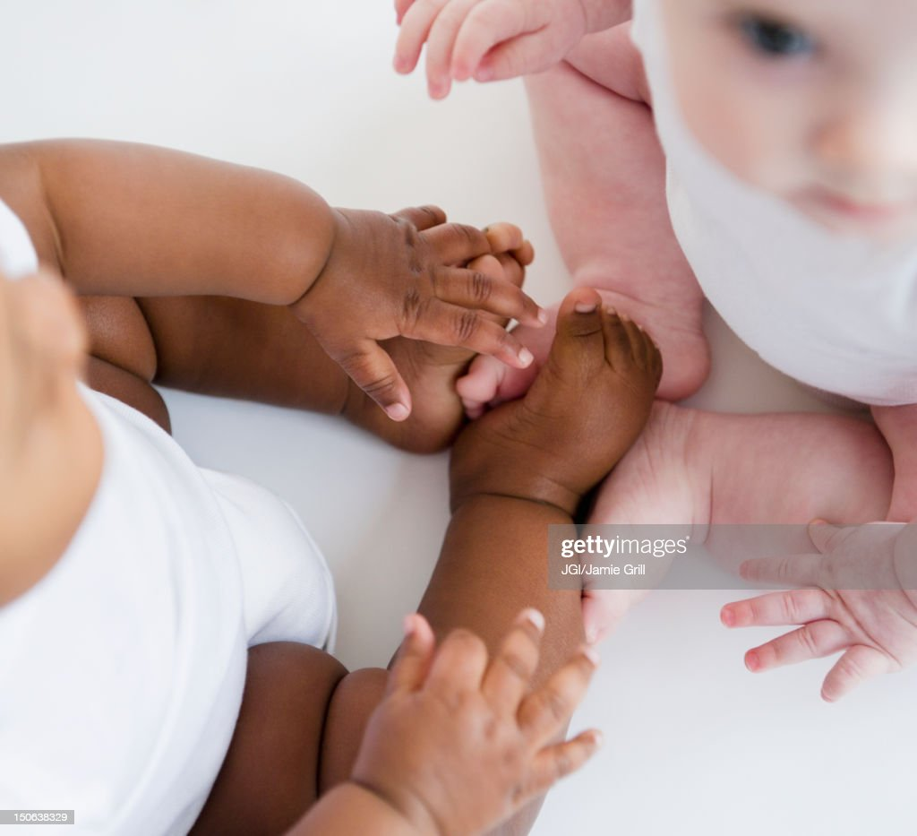 Babies sitting together on floor : Stock Photo