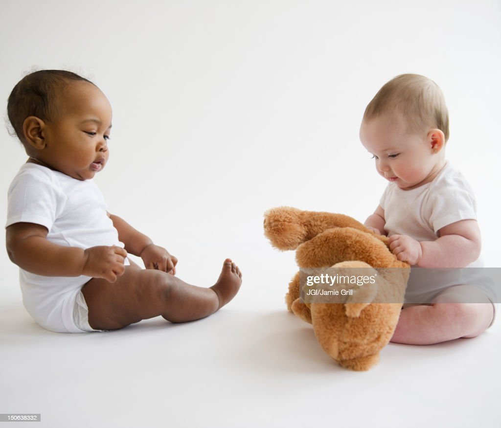 Babies sitting together on floor with teddy bear : Stock Photo