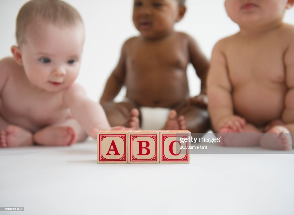 Babies sitting with alphabet blocks : Stock Photo