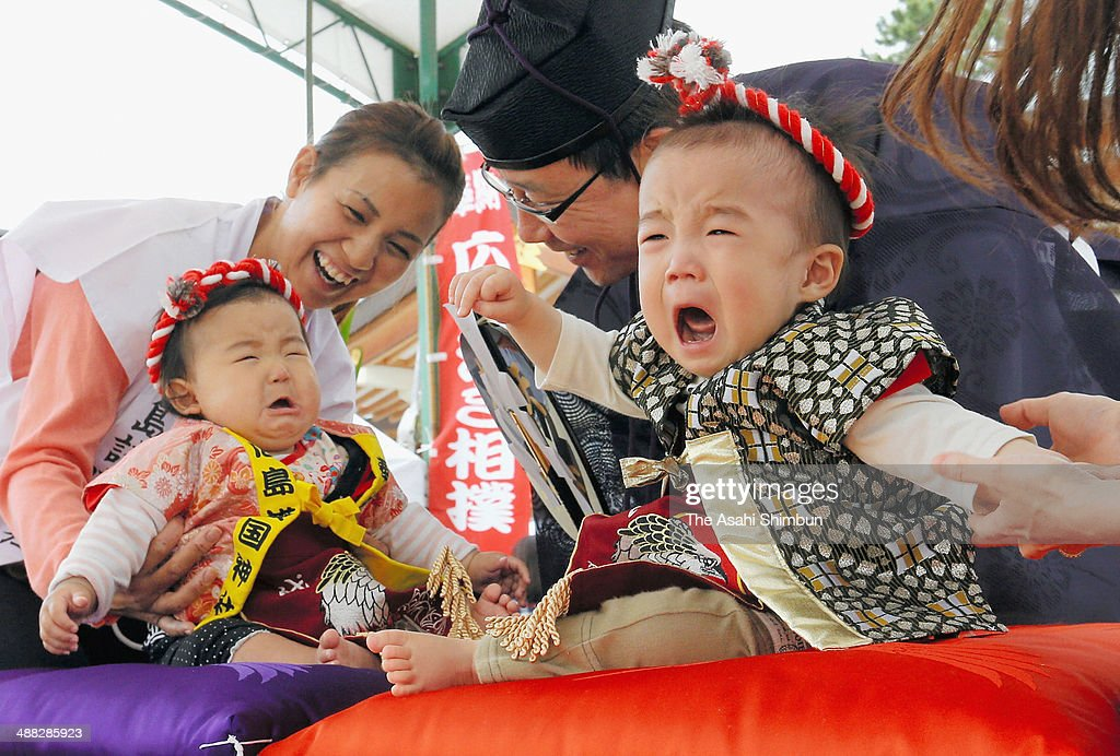 Babies start crying during the 'Baby-Cry Sumo' at Gokoku Shrine on May 5, 2014 in Hiroshima, Japan. The first baby to cry wins the competition. The ceremony takes place in Japan to wish for the good health of the child as it is said that crying is good for the health of babies.