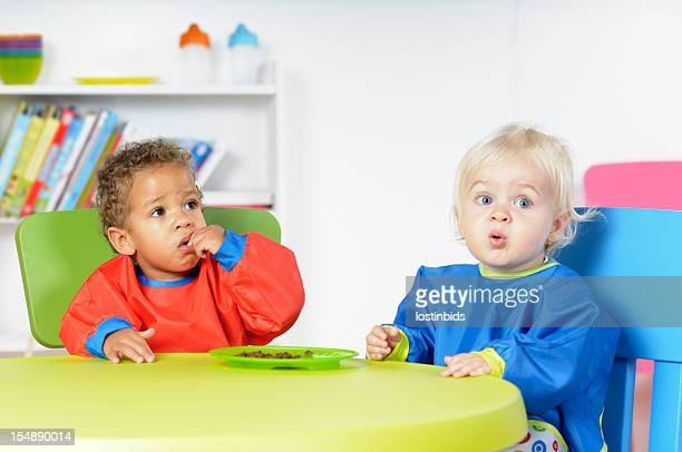 Babies/ Toddlers  At Mealtime In A Nursey Setting