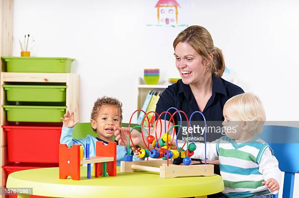 Babies/ Toddlers Enjoying Playtime With Carer/ Childminder