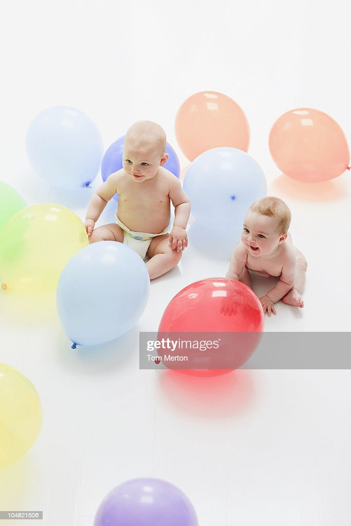 Babies with balloons on floor : Stock Photo