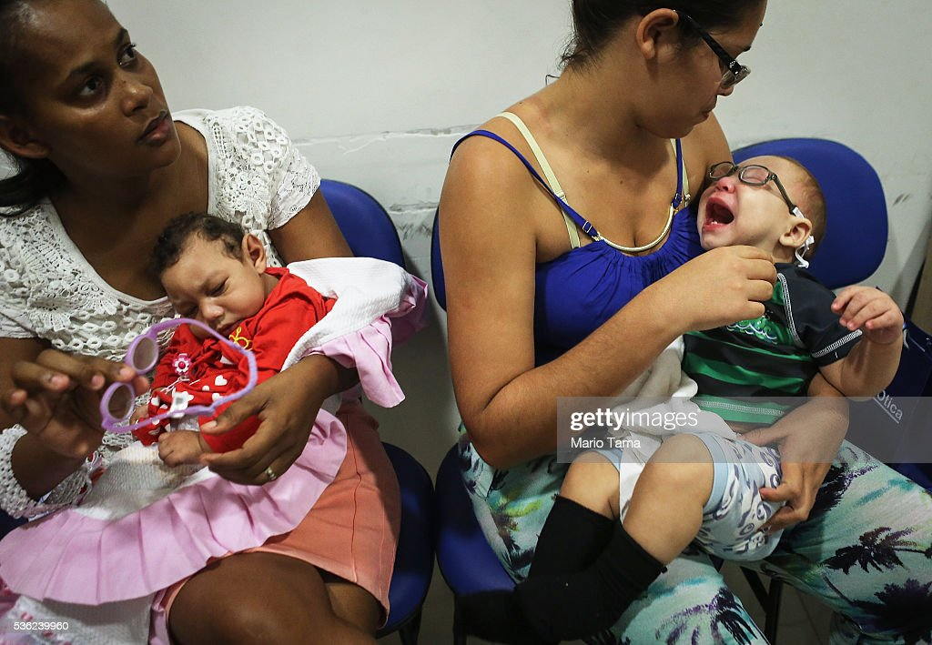 Babies with microcephaly David Henrique Ferreira (R) and Sofia Valentine (L) are tested with new glasses with their mothers Mylene (R) and Vera on May 31, 2016 in Recife, Brazil. Microcephaly is a birth defect linked to the Zika virus where infants are born with abnormally small heads. Vision problems have been reported in some of the infants as well. The city of Recife and surrounding Pernambuco state remain the epicenter of the Zika virus outbreak, which has now spread to many countries in the Americas. A group of health experts recently called for the Rio 2016 Olympic Games to be postponed or cancelled due to the Zika threat but the WHO (World Health Organization) rejected the proposal. The Olympic torch passed through Recife today.