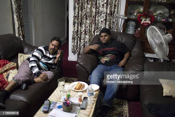 Bablu Sheikh sits with his father left watching television February 25 2011 at his home in the Queens borough of New York Bablu a BangladeshiAmerican...