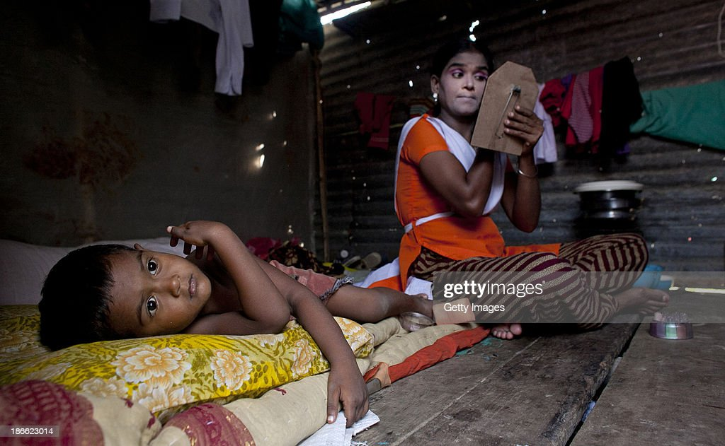 Baby Akhter Sultang applies makeup as her 3 year old son, Shobujh, lays on their bed at the Olympic Circus, November 1, 2013 in Jamsha, Bangladesh. Baby, who doesn't know her age, grew up in the circus without ever having the chance to attend school. She has been performing for 6 years, does not enjoy performing but says she stays because she needs the money. Generations of low income families are born into circuses with rarely the hope of ever working in different profession or escaping the harsh realities of the circus. The children, often very young, are trained to be full working members usually without the opportunity for an education. As modernization slowly takes over landscape of Bangladesh, the circus is a dying art form and is moving further and further away from mainstream entertainment.