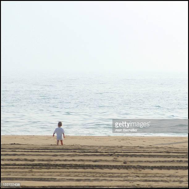 Baby alone on beach facing sea