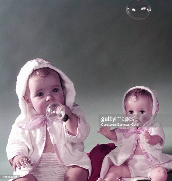 A baby and a Bannister Baby Doll blowing bubbles 16th September 1954