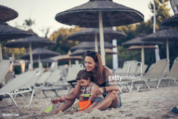 Baby and mother in sand