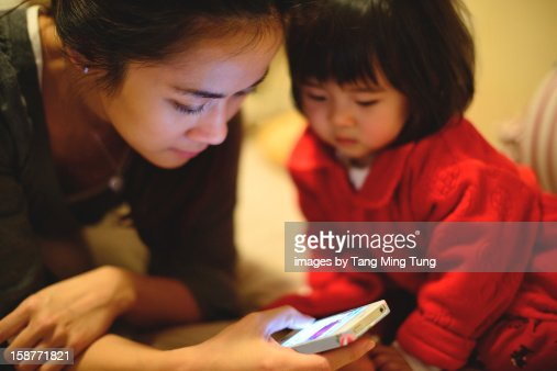 baby and pretty young mom using smartphone on bed : Stock Photo