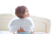 Baby girl is sitting on bed, wearing small fluffy angel wings. Rear view.