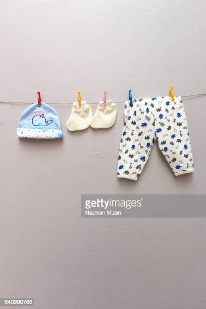 Baby apparels on clotheslines on plain gray background. Shot on portrait format.