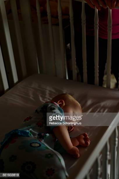 Baby asleep in crib at night with mom beside crib