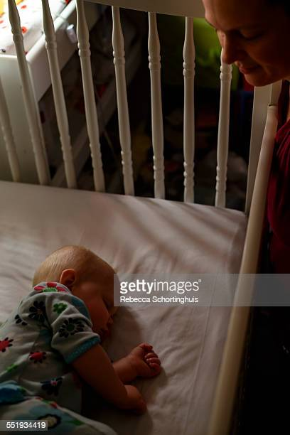 Baby asleep in crib at night with mom watching