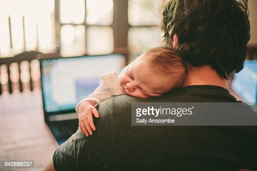 Baby asleep on fathers shoulder