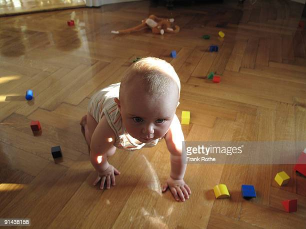 Baby at a beautiful wooden floor in the child room