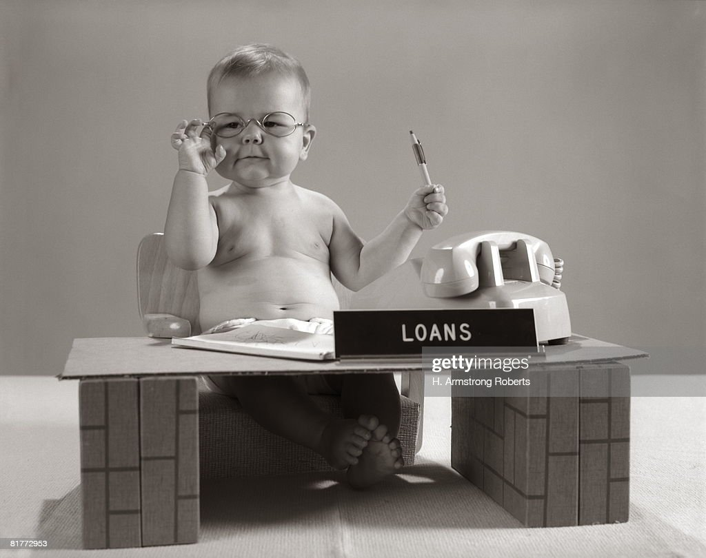 Baby At Desk Playing Loan Officer. : Stock Photo