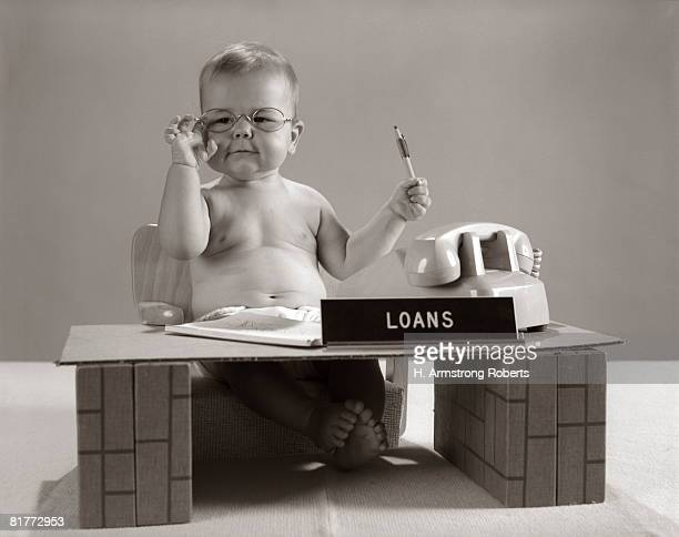 Baby At Desk Playing Loan Officer.