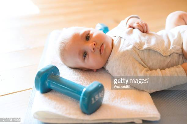 Baby at home lying on mat next to dumbbells