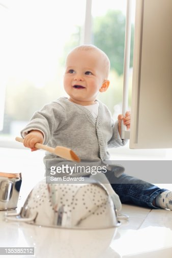Baby banging on colander with wooden spoon : Stock Photo